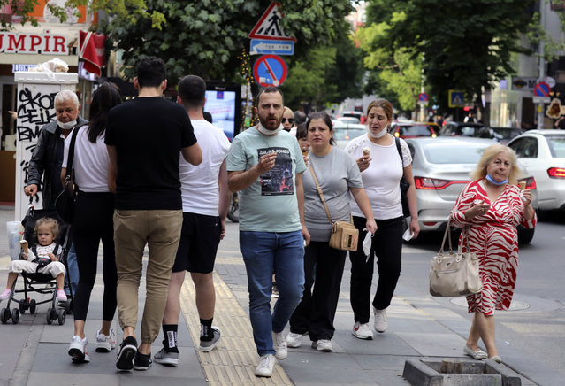 People who are not wearing face masks to protect against the spread of coronavirus, walk in city the centre, in Ankara, Turkey, Sunday, June 21, 2020. Turkish authorities have made the wearing of masks mandatory in three major cities to curb the spread of COVID-19 following an uptick in confirmed cases since the reopening of many businesses. (Photo by Burhan Ozbilici/AP Photo)