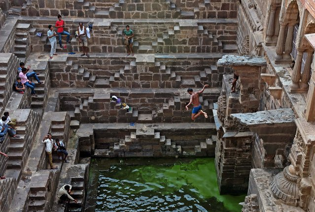 An Indian youth jumps into the water of the historic Chand Baori stepwell as others look on in Abhaneri village of western Rajasthan state on September 24, 2015. For a few hours on one day each year, local residents are permitted to descend into the 100-foot-deep, 1,200-year-old stepwell, as Hindu devotees in the area mark a local festival, at the same time as Hindus worldwide observe Ganesh Chaturthi festivities. (Photo by Alex Ogle/AFP Photo)