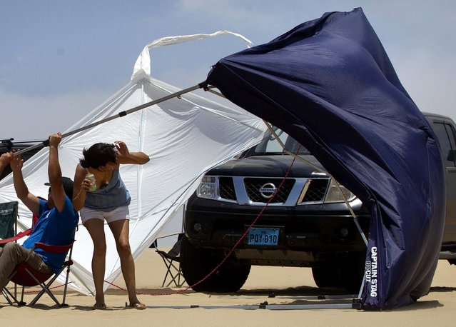 A tent is blown away by strong gusts of wind as spectators watch the 1st stage near Pisco, Peru. (Photo by Victor R. Caivano/Associated Press)