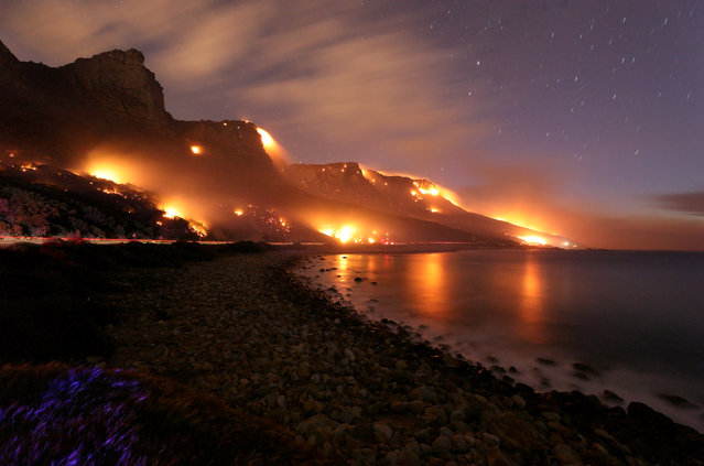 Wildfires burn along the Twelve Apostles area of Table Mountain in Cape Town, South Africa, October 13, 2017. (Photo by Mike Hutchings/Reuters)