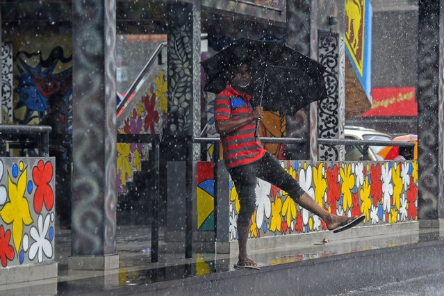 A local resident shelters under an umbrella during a downpour in Colombo's suburb of Dompe on July 20, 2020. (Photo by Ishara S. Kodikara/AFP Photo)