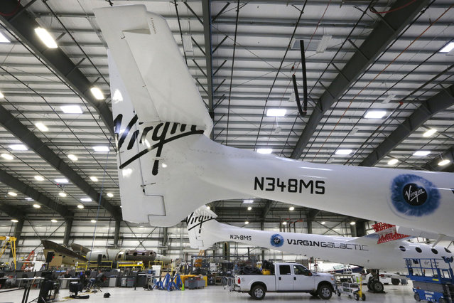 Virgin Galactic's new spaceship N202VG (bottom L) is seen behind the WhiteKnightTwo carrier aircraft mothership (front), which landed safely after splitting from SpaceShipTwo, in a hangar at Mojave Air and Space Port in Mojave, California, November 4, 2014. (Photo by Lucy Nicholson/Reuters)