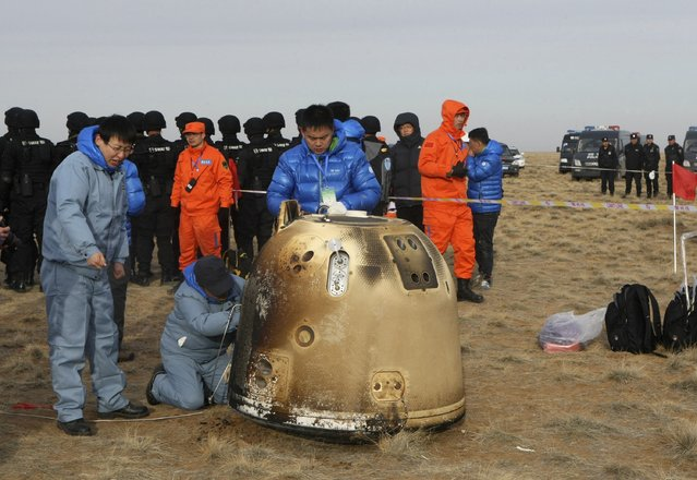 Researchers examine the return capsule of China's test lunar orbiter after it landed in Siziwang Banner, Inner Mongolia Autonomous Region November 1, 2014. The return capsule of China's test lunar orbiter landed successfully early Saturday morning in north China's Inner Mongolia, making China the third nation in the world able to send a lunar orbiter and have it return to Earth. (Photo by Reuters/Stringer)