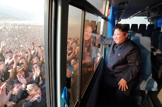 This picture released from North Korea's official Korean Central News Agency (KCNA) on October 8, 2015 shows North Korean leader Kim Jong-Un (R) waving to a crowd from a bus while inspecting a newly-built village at Paekhak-dong in Sonbong District of flood-hit Rason City. (Photo by AFP Photo/KCNA via KNS)