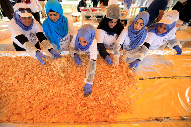 Women arrange cooked fish into a huge container during an attempt to enter the Guinness Book of World Records for the largest spicy fish plate in Sarafand, South Lebanon September 16, 2016. The plate contains around 802 kilograms of spicy fish, organisers said. (Photo by Ali Hashisho/Reuters)