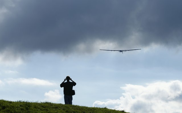 A man watches a test flight of the solar-powered Solar Impulse 2 experimental aircraft, piloted by Swiss Bertrand Piccard, in Payerne November 13, 2014. (Photo by Ruben Sprich/Reuters)