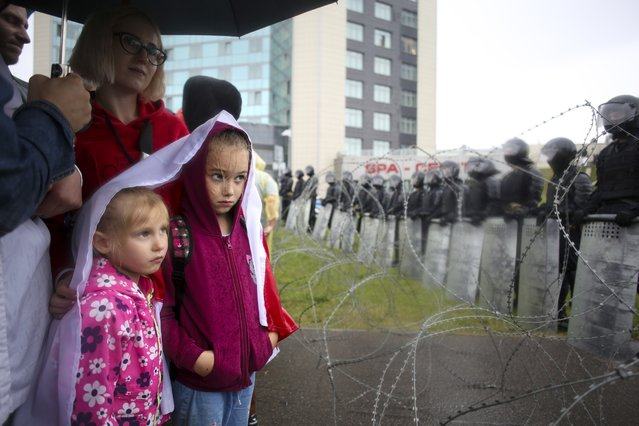 People with their childs stand at a barbed wire fence in front of a police line toward the Independence Palace, residence of the President Alexander Lukashenko, during Belarusian opposition supporters rally in Minsk, Belarus, Sunday, September 6, 2020. Sunday's demonstration marked the beginning of the fifth week of daily protests calling for Belarusian President Alexander Lukashenko's resignation in the wake of allegedly manipulated elections. (Photo by TUT.by/AP Photo)