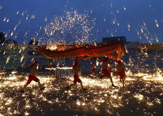 Dancers perform a fire dragon dance in the shower of molten iron spewing firework-like sparks during a folk art performance to celebrate traditional Chinese Spring Festival at an amusement park in Beijing February 10, 2013. The Lunar New Year, or Spring Festival, begun on February 10 and marked the start of the Year of the Snake, according to the Chinese zodiac. (Photo by Kim Kyung-Hoon/Reuters)