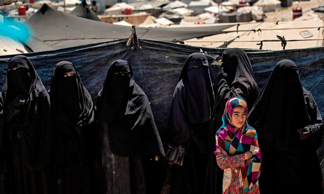 A girl stands in a line of women at the Kurdish-run al-Hol camp in the al-Hasakeh governorate in northeastern Syria on August 18, 2020, where families of Islamic State (IS) foreign fighters are held. (Photo by Delil Souleiman/AFP Photo)