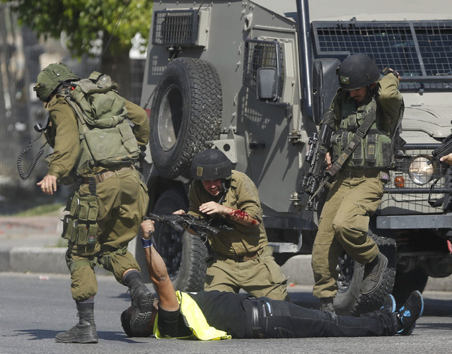 In this Friday, October 16, 2015 file photo, an Israeli soldier runs to help another who was just stabbed by a Palestinian, seen on the ground holding a knife, during clashes in Hebron, West Bank. (Photo by Nasser Shiyoukhi/AP Photo)