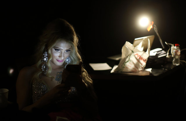In this Sunday, September 18, 2016 photo, Paris Nemc from Slovakia, looks at her phone during an interval at Miss Trans Star International 2016 show celebrated in Barcelona, Spain. (Photo by Manu Fernandez/AP Photo)