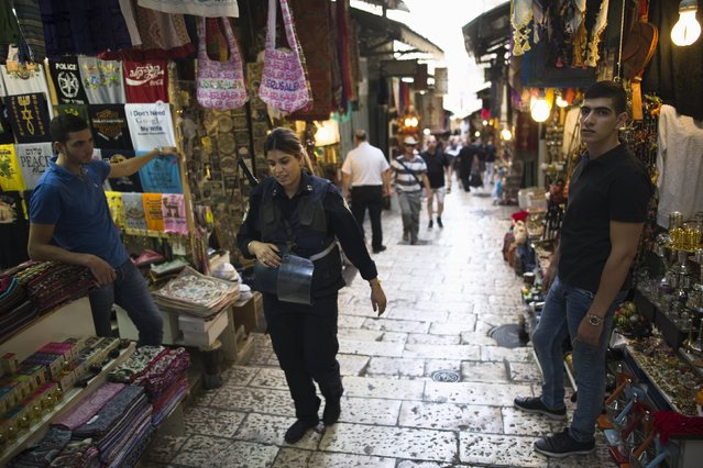 An Israeli police officer (C) walks past vendors in Jerusalem's Old City October 18, 2015. A surge in Palestinian attacks in Israel is raising concerns that the weakening economy could eventually be pushed into recession. Picture taken October 18, 2015. (Photo by Amir Cohen/Reuters)
