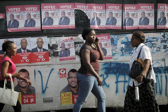 Women walk next to posters of candidates running for elections plastered on a bus along a street in Port-au-Prince, Haiti, October 20, 2015. Haiti will hold elections on October 25. (Photo by Andres Martinez Casares/Reuters)