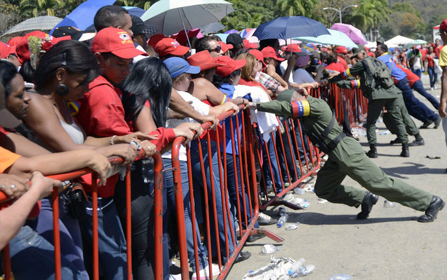 Venezuelan soldiers push the protective fences as supporters wait in line to pay last respects to the late Venezuelan President Hugo Chavez, outside the Military Academy in Caracas on March 7, 2013. Venezuelans filed past the open casket of late President Hugo Chavez as he lay in state  after throngs of weeping loyalists gave the firebrand leftist a rousing farewell on the streets on the eve. (Photo by Leo Ramirez/AFP Photo)