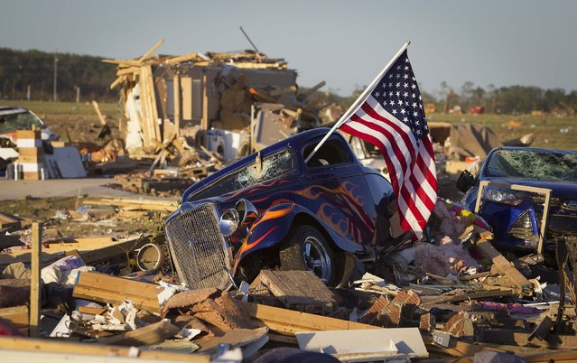A U.S. flag sticks out the window of a damaged hot rod car in a suburban area after a tornado near Vilonia, Arkansas in this April 28, 2014 file photo. I was covering the tornados that swept though Arkansas and other states killing 35 people and I decided to drive out to Vilona, an area that had suffered some of the worst damage, having seen it from a plane. (Photo and caption by Carlo Allegri/Reuters)