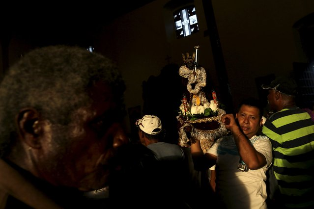 A worshipper of the Black Christ of Portobelo carries a small statute of the Black Christ during the annual celebratory pilgrimage in Portobelo, in the province of Colon October 21, 2015. (Photo by Carlos Jasso/Reuters)