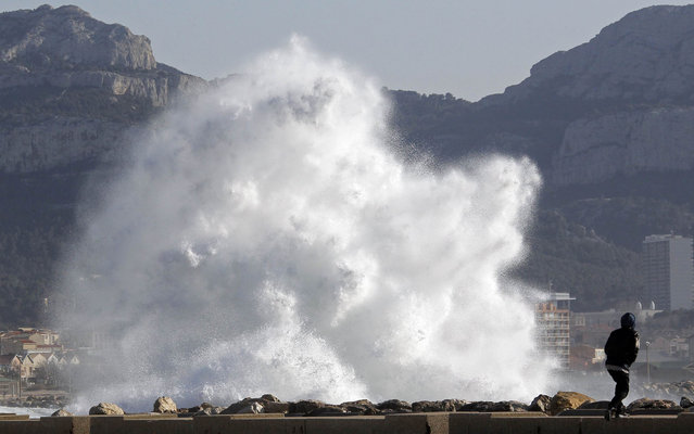 A passer-by walks as a high wave hits the waterfront in Marseille March 14, 2013. French public weather agency Meteo France issued an orange alert warning of winds threatening southern French departments. (Photo by Jean-Paul Pelissier/Reuters)