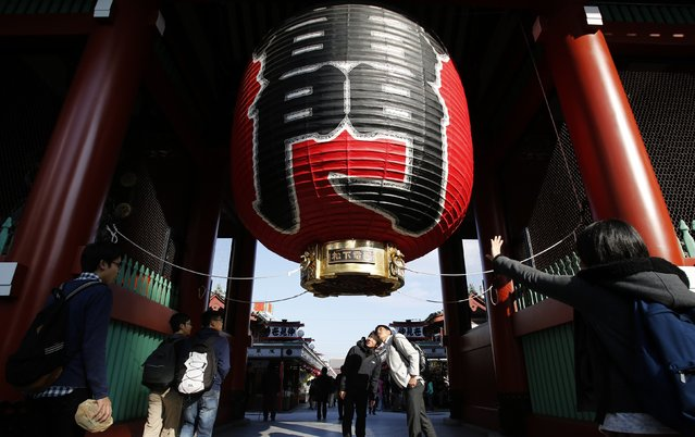 Visitors look at a huge lantern at the Kaminarimon gate at the start of Nakamise shopping street on Asakusa district in Tokyo November 28, 2014. Tokyo is a place of pulsing clubs, steep-roofed temples, narrow lanes packed with smoky restaurants where meat sizzles on grills and karaoke pubs whose yowled anthems spill into the streets. (Photo by Yuya Shino/Reuters)