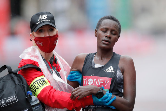 Edith Chelimo (R) of Kenya walks with a medical assistant after finishing the elite women's race during the London Marathon in London, Britain, 04 October 2020. (Photo by Tom Jenkins/The Guardian)