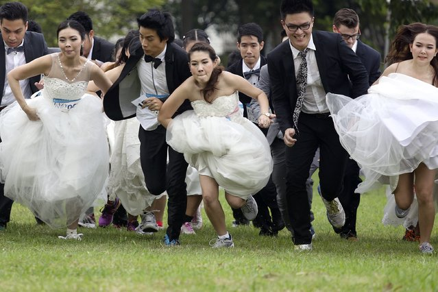 "Couples participate in the ""Running of the Brides"" race in a park in Bangkok November 29, 2014. (Photo by Damir Sagolj/Reuters)"