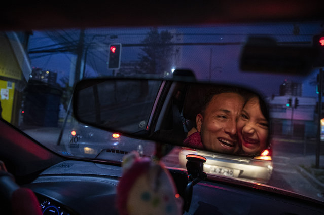 Reflected in the rearview mirror, Jose Collantes gets a hug from daughter Kehity while they're stopped at a red light, as Jose drives his five-year-old home from a playdate in Santiago, Chile, Sunday, September 6, 2020, three months after they lost his wife, her mother, to COVID-19. Their case highlights how COVID-19 deaths the world over are often the beginning of a new personal journey for those affected. (Photo by Esteban Felix/AP Photo)