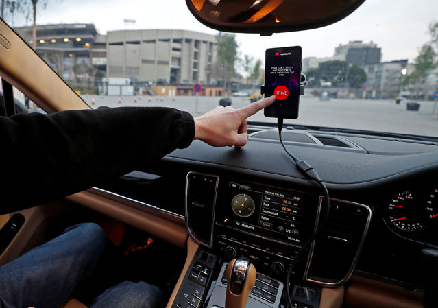 An engineer points to a Huawei Mate 10 Pro mobile used to control a driverless car during the Mobile World Congress in Barcelona, Spain, February 26, 2018. (Photo by Yves Herman/Reuters)
