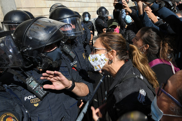 Demonstrators protest in front of Catalan regional police during a demonstration on October 16, 2020 in Barcelona to protest against the new restrictions imposed by the regional government on bars and restaurants to fight against COVID-19 disease. Bars and restaurants are to be closed across Spain's northeastern Catalonia region for the next 15 days to slow rising coronavirus infections, the regional government said on October 14, 2020. The move comes as Spain battles one of the highest rates of infection in the European Union, with nearly 900,000 infections and more than 33,000 deaths. (Photo by Lluis Gene/AFP Photo)