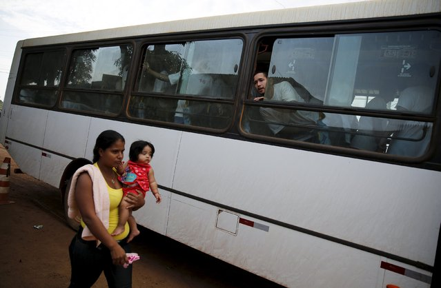 A woman walks with her baby as Cleverson Barbosa, 27, tells her that her husband cannot go to the ACUDA programme, at a complex of ten prisons in Porto Velho, Rondonia State, Brazil August 28, 2015. (Photo by Nacho Doce/Reuters)