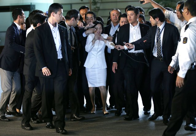 Japan's Justice Minister Midori Matsushima (C) reacts as she is surrounded by reporters upon her arrival at Prime Minister Shinzo Abe's official residence for a meeting with Abe in Tokyo, in this October 20, 2014 file photo. (Photo by Toru Hanai/Reuters)