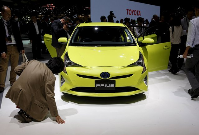 People look at Toyota Motor Corp new Prius hybrid car at the 44th Tokyo Motor Show in Tokyo, Japan, October 28, 2015. (Photo by Toru Hanai/Reuters)