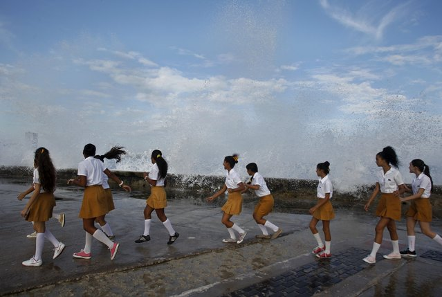 "Students play as waves crash on Havana's seafront boulevard ""El Malecon"" during a gathering in honour of rebel hero Camilo Cienfuegos, October 28, 2015. Cienfuegos was a commander of Fidel Castro's rebel army but died less than a year after their victory when his plane disappeared over the ocean on October 28, 1959 enroute from Havana to Camaguey. (Photo by Reuters/Stringer)"