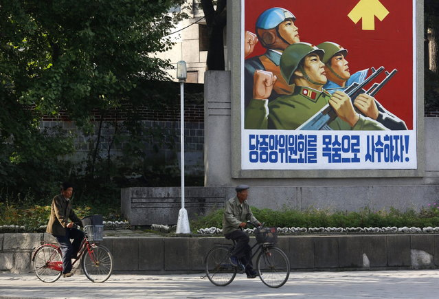 In this September 22, 2012 photo, North Koreans ride bicycles past a propaganda poster in Kaesong, North Korea. Kaesong, which sits just north of the Demilitarized Zone separating North Korea and South Korea, was the ancient capital of the Koryo Dynasty for 500 years until 1392. (Photo by Vincent Yu/AP Photo)