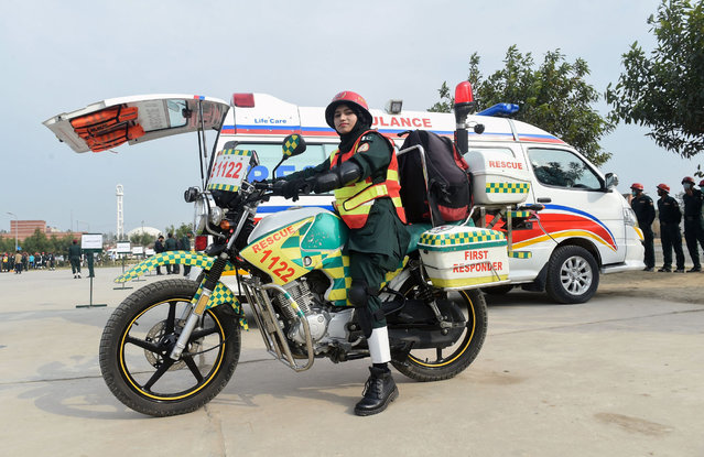 Pakistani first responder Samra Akram Zia poses for a photograph with her motorcycle ambulance service during a passing out ceremony in Lahore on February 24, 2018. (Photo by Arif Ali/AFP Photo)