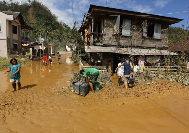 Filipino typhoon victims walk through heavy mud in the typhoon hit town of Taft, Samar island, Philippines, 08 December 2014. Typhoon Hagupit weakened into a tropical storm as it moved towards the Philippine capital after killing at least 27 people and displacing more than one million people in the eastern and central provinces. (Photo by Francis R. Malasig/EPA)