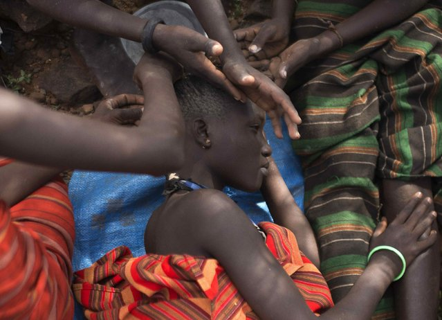 A Pokot girl gets her braids done by her friends prior to an initiation ceremony marking her passing over into womanhood, about 80 km (50 miles) from the town of Marigat in Baringo County, December 5, 2014. (Photo by Siegfried Modola/Reuters)