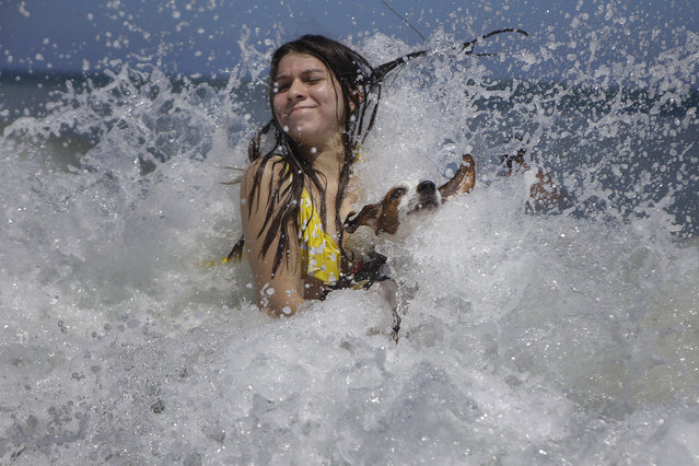 Mariana Rojas plays with her dog Sussy in the waves off Los Angeles beach after it recently reopened following a lockdown to contain the spread of COVID-19 in La Guaira, Venezuela, Friday, October 23, 2020. Strict quarantine restrictions forced the closure of beaches across the country in March and reopened this week. (Photo by Matias Delacroix/AP Photo)