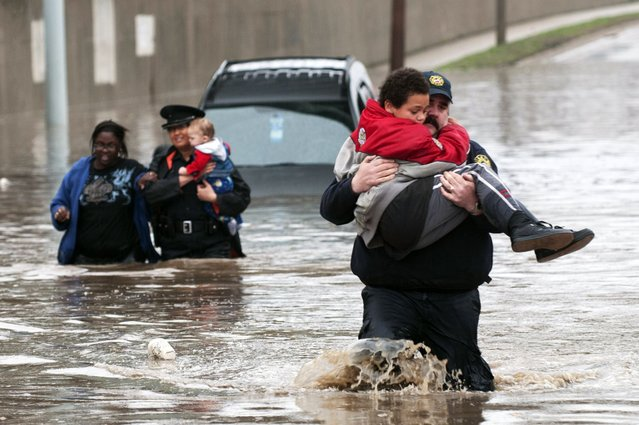 Firefighter Jason Kelley and police officer Shannon Vandenheuvel carry children from Barbara Jones' partially submerged car in Grand Rapids, Mich. Thursday, April 18, 2013. Middle America was getting everything nature has to throw at it on Thursday, from snow in the north to tornadoes in the Plains, and with torrential rains causing floods and transportation chaos in several states. (Photo by Chris Clark/AP Photo/Grand Rapids Press)