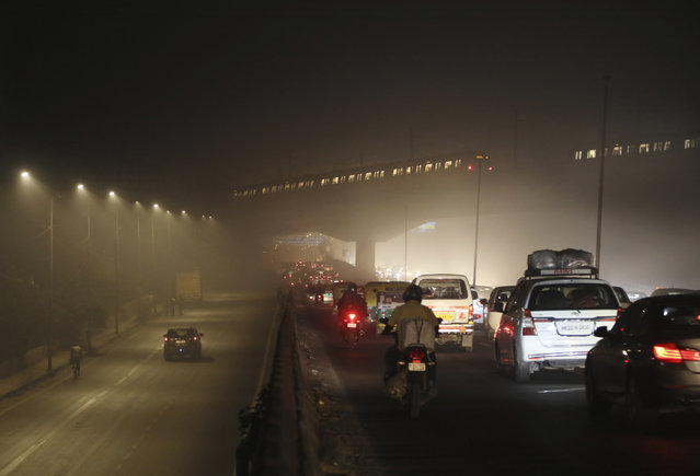 Commuters drive on a road engulfed in smog in New Delhi, India, Thursday, November 5, 2020. A thick quilt of smog lingered over the Indian capital and its suburbs on Friday, fed by smoke from raging agricultural fires that health experts worry could worsen the city's fight against the coronavirus. Air pollution in parts of New Delhi have climbed to levels around nine times what the World Health Organization considers safe, turning grey winter skies into a putrid yellow and shrouding national monuments. (Photo by Manish Swarup/AP Photo)