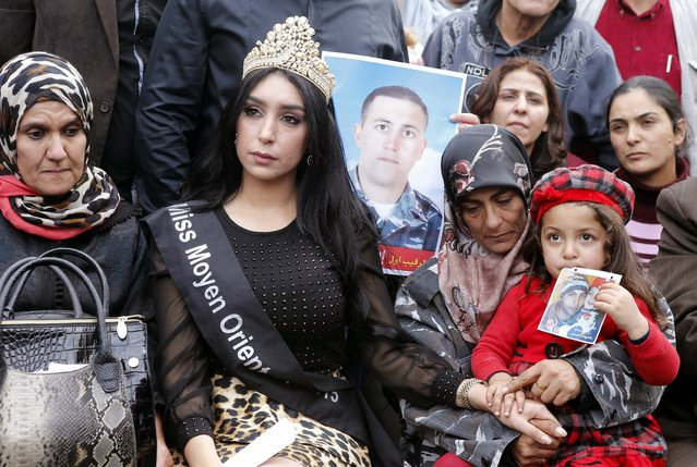 The mother and child (R) of Lebanese soldier Ali al-Bazzal, who was killed by Syria's al Qaeda offshoot Nusra Front, sit beside Miss Middle East (C) and other protesters as they demand the release of remaining soldiers, pressuring the government to act, in downtown Beirut December 14, 2014. (Photo by Mohammed Azakir/Reuters)