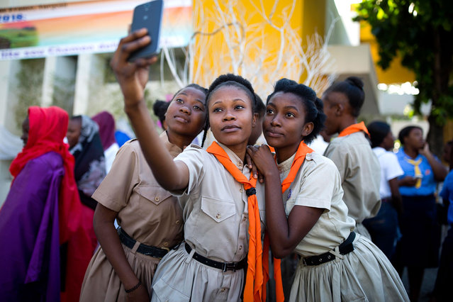 Girl scouts pose for a group photo at the third station of the Way of the Cross reenactment marking Good Friday, in Port-au-Prince, Haiti, Friday, March 30, 2018. Thousands of Haitians are commemorating the crucifixion of Jesus Christ by reenacting the Way of the Cross, visiting the 14 stations, each marking an event that befell Jesus Christ on his final journey. (Photo by Dieu Nalio Chery/AP Photo)