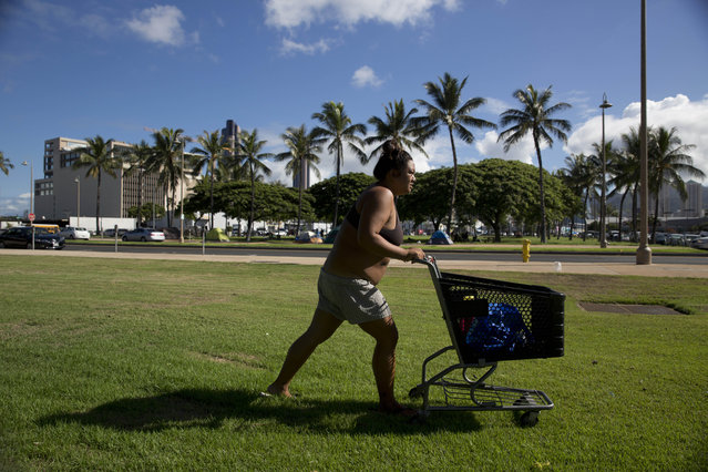 In this Wednesday, August 26, 2015 photo, Deja-Lynn Rombawa-Quarles, a 24-year-old homeless woman who works part time at an elementary school as a group leader, pushes her cart to do laundry at a homeless encampment in the Kakaako district of Honolulu. Rombawa-Quarles is one of a growing number of working poor in Honolulu who, through a combination of high housing costs, a dearth of affordable housing and bad circumstances, wound up living on the street. (Photo by Jae C. Hong/AP Photo)