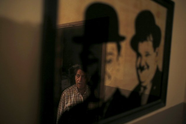 Projectionist Antonio Feliciano, 75, is reflected in a picture of actors Laurel and Hardy, at Girasol cinema in Vila Nova de Milfontes, Portugal May 8, 2014. (Photo by Rafael Marchante/Reuters)