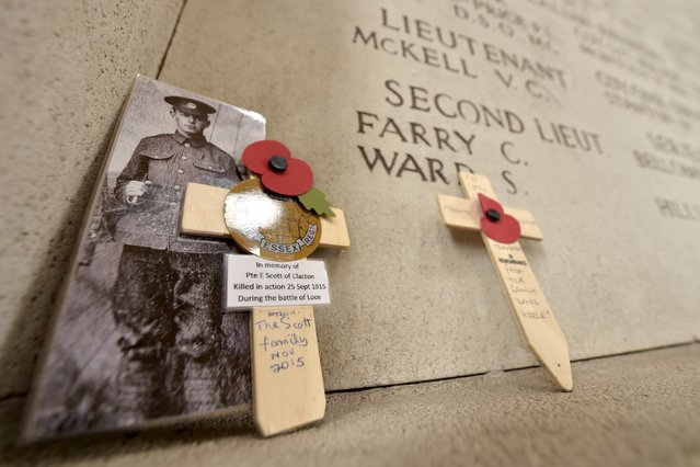A picture is seen in front of a wall displaying the names of Commonwealth soldiers who died in World War One during the Armistice Day commemorations at the Menin Gate in Ypres. (Photo by Eric Vidal/Reuters)