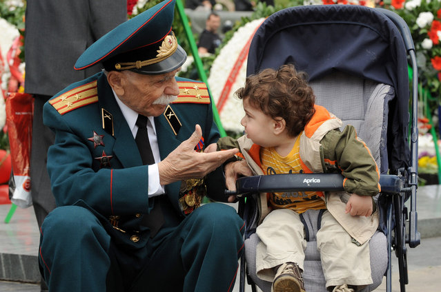 A World War II veteran speaks with a little child during Victory Day celebration in the Armenian capital Yerevan. Armenia as well as the other former Soviet republics celebrates the 1945 victory over Nazi Germany, the date of the Nazis' capitulation to the Soviet Union, which took place in the evening on May 8, 1945 (May 9 by Moscow Time), following the original capitulation Germany agreed earlier to the joint Allied forces on the Western Front.  (Photo by Karen Minasyan/Getty Images)
