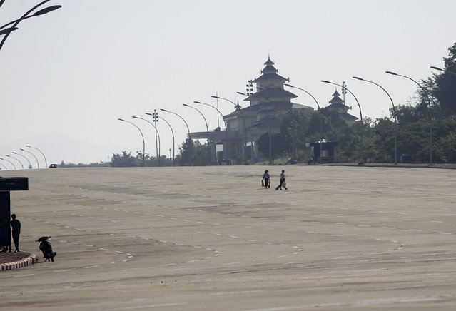 Workers work on the almost empty twenty lanes road in front of parliament in Naypyitaw November 14, 2015. (Photo by Soe Zeya Tun/Reuters)