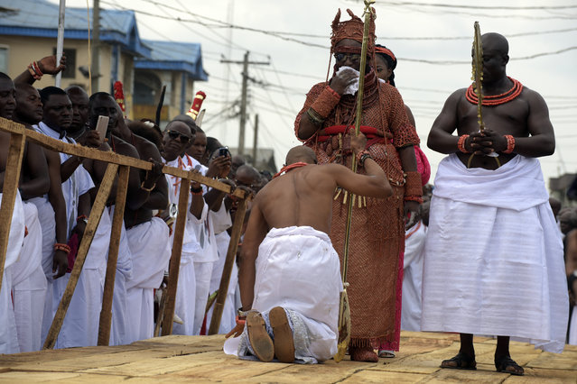 A palace aide kneels down before newly crowned 40th Monarch of the Benin kingdom Oba Ewuare II (C) on a wooden bridge during a rite to mark his coronation in Benin City, midwest Nigeria, on October 20, 2016. The crowning of the 40th Monarch of the ancient Benin kingdom marks the end of weeklong activities surrounding the coronation of the Oba of Benin. (Photo by Pius Utomi Ekpei/AFP Photo)