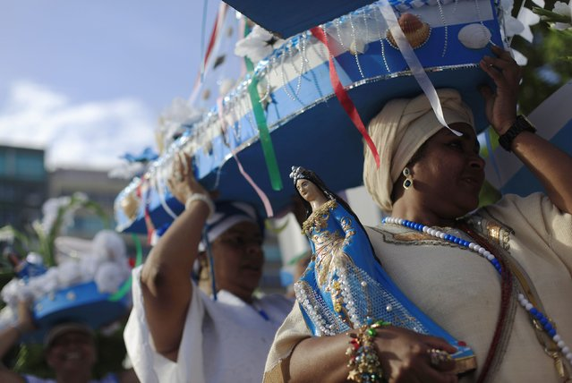 Followers of the Afro-Brazilian religion Umbanda carry offerings and an image of Iemanja, goddess of the sea, in Copacabana Beach in Rio de Janeiro December 29, 2014. (Photo by Ricardo Moraes/Reuters)