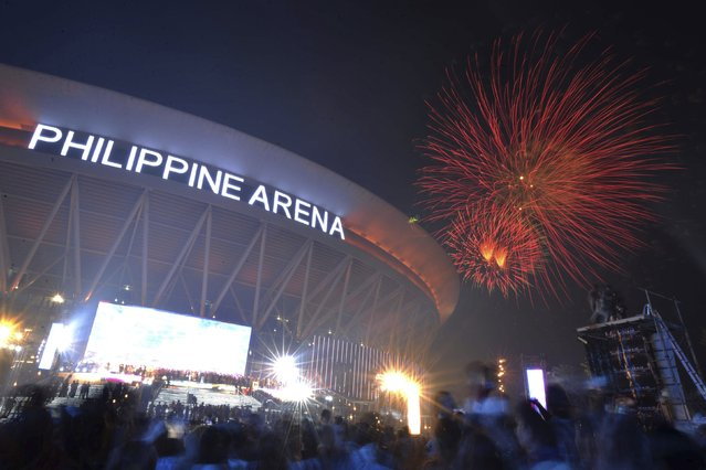 Spectators watch as fireworks light the sky during New Year celebrations outside the Philippine Arena in Bocaue town, Bulacan province, north of Manila January 1, 2015. (Photo by Ezra Acayan/Reuters)
