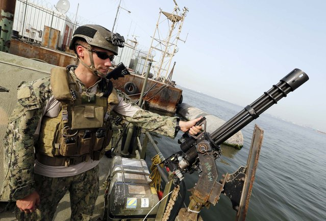 A U.S. Navy officer stands guard on Riverine Command Boat during a media tour ahead of the International Mine Countermeasures Exercise (IMCMEX), at the Bahrain Navy sea port in Manama May 12, 2013. Representatives from more than 40 nations will gather in Bahrain and waters of the Gulf region for the exercise, which is considered the largest exercise of its kind in the region. A British Royal Navy spokesperson said that it will be the first time for the British Royal Navy to head the entire exercise. (Photo by Hamad I Mohammed/Reuters)