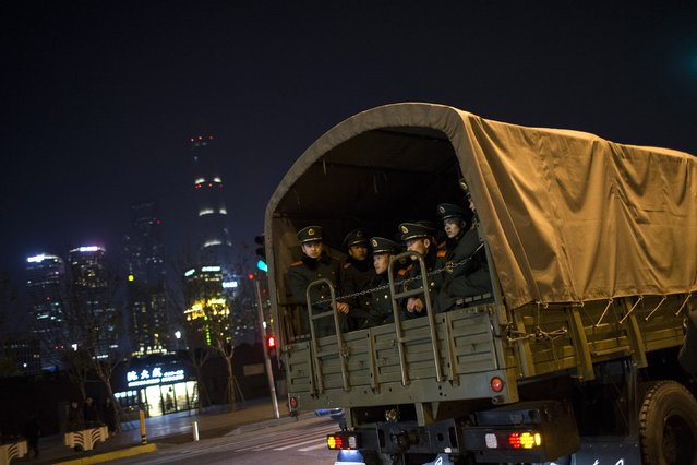 Paramilitary police officers sit on a truck leaving the location where people were killed in a stampede incident during a New Year's celebration on the Bund, in Shanghai January 1, 2015. (Photo by Aly Song/Reuters)